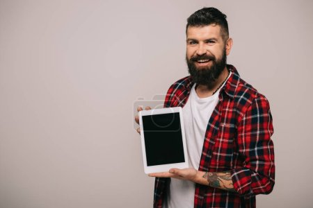 smiling man in checkered shirt showing digital tablet with blank screen, isolated on grey