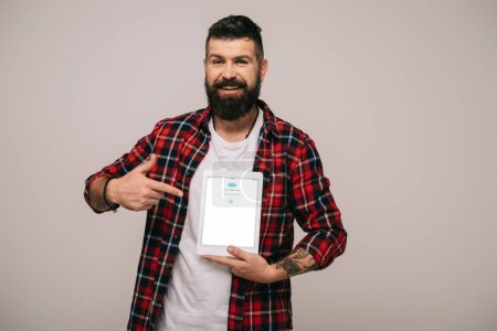 bearded man in checkered shirt pointing at digital tablet with skype app, isolated on grey