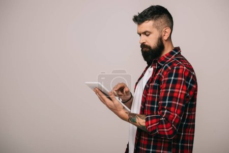 Photo for Handsome bearded man in checkered shirt using digital tablet, isolated on grey - Royalty Free Image