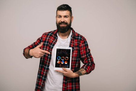 Photo for Smiling man pointing at digital tablet with infographic app, isolated on grey - Royalty Free Image
