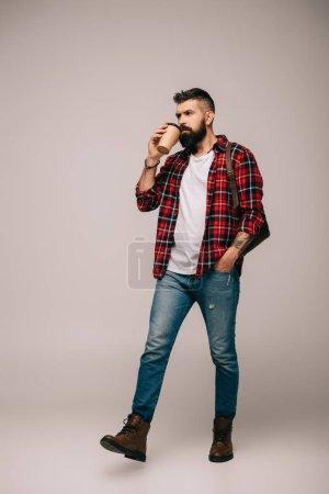 Photo pour Homme barbu en chemise à carreaux marche et boire du café pour aller isolé sur gris - image libre de droit