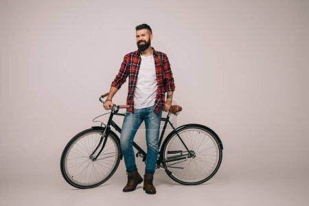 Photo pour Homme heureux en chemise à carreaux posant avec vélo sur gris - image libre de droit