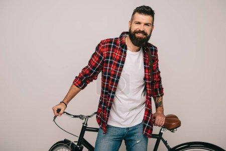 Photo pour Bel homme souriant, posant avec vélo isolé sur fond gris - image libre de droit