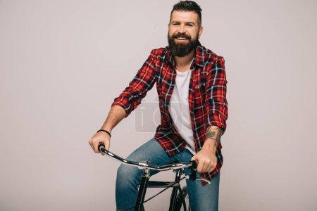 Photo pour Bel homme souriant à vélo isolé sur gris - image libre de droit
