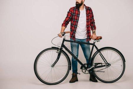 Photo pour Vue recadrée de l'homme en chemise à carreaux posant avec vélo sur gris - image libre de droit