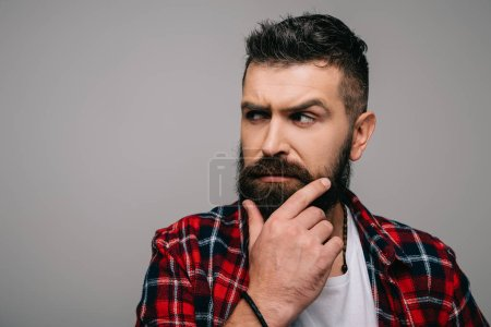 Foto de Hombre barbudo sospechoso en el pensamiento de camisa a cuadros aislado en gris - Imagen libre de derechos