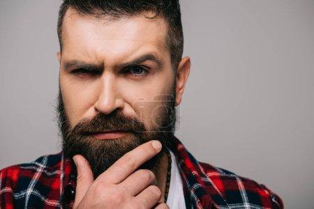 Foto de Hombre barbudo sospechoso mirando a cámara aislada en gris - Imagen libre de derechos