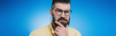 Foto de Hombre barbudo sospechoso en gafas mirando a cámara aislada en azul - Imagen libre de derechos