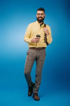 homme souriant avec café à emporter et sac à dos isolé sur bleu