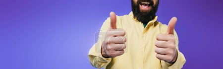 Photo pour Vue recadrée de l'homme souriant montrant pouces vers le haut isolé sur violet - image libre de droit
