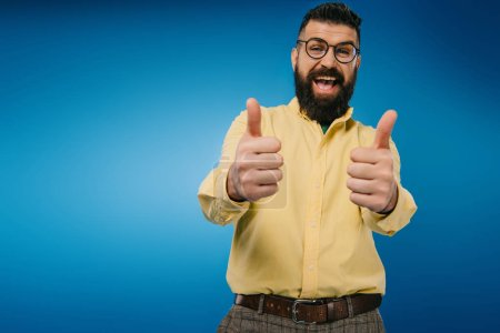 excited bearded man in eyeglasses showing thumbs up isolated on blue