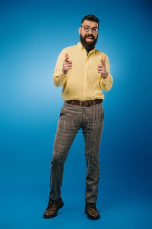 Photo for Handsome excited man pointing at you isolated on blue - Royalty Free Image