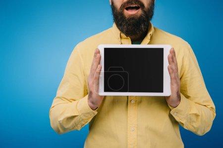 Ausgeschnittene Ansicht eines aufgeregten Mannes, der ein digitales Tablet mit leerem Bildschirm zeigt, isoliert auf blau