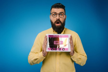 Photo for Shocked bearded man presenting digital tablet with online tickets app, isolated on blue - Royalty Free Image