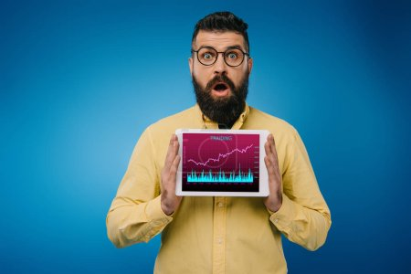 Photo for Shocked bearded man presenting digital tablet with tariding app, isolated on blue - Royalty Free Image