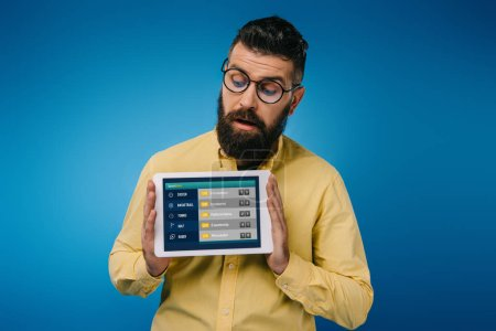 interested bearded man looking at digital tablet with sport app, isolated on blue
