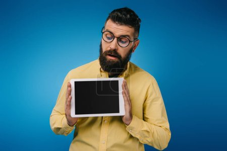 interested bearded man looking at digital tablet with blank screen, isolated on blue