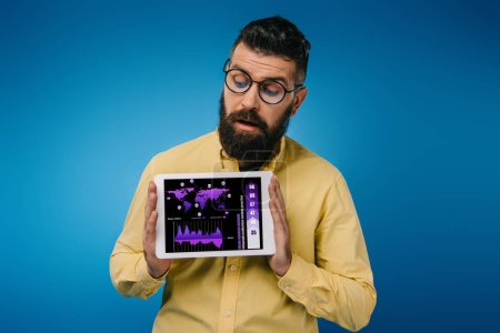 interested bearded man looking at digital tablet with infographic, isolated on blue