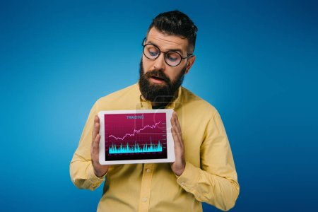 Photo for Interested bearded man looking at digital tablet with tariding app, isolated on blue - Royalty Free Image