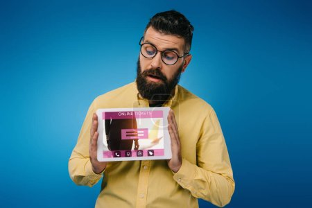 Photo for Interested bearded man looking at digital tablet with online tickets app, isolated on blue - Royalty Free Image