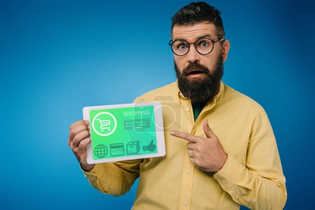 shocked bearded man pointing at digital tablet with shopping app, isolated on blue