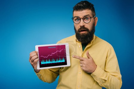 shocked bearded man pointing at digital tablet with tariding app, isolated on blue