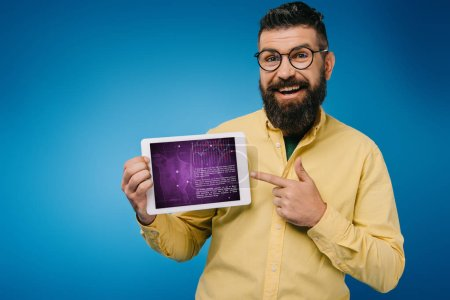 Photo for Cheerful bearded man pointing at digital tablet with infographic, isolated on blue - Royalty Free Image
