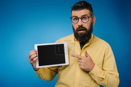 interested bearded man pointing at digital tablet with blank screen, isolated on blue