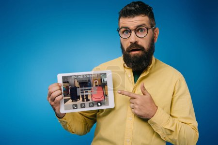 Photo for Shocked bearded man pointing at digital tablet with online booking app, isolated on blue - Royalty Free Image