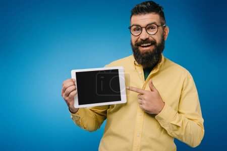 Photo for Handsome smiling man pointing at digital tablet with blank screen, isolated on blue - Royalty Free Image