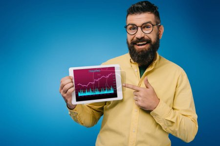 Photo for Happy bearded man pointing at digital tablet with tariding app, isolated on blue - Royalty Free Image