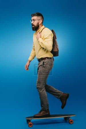 Photo pour Homme barbu skateboard en studio sur bleu - image libre de droit