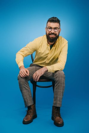 Photo for Smiling bearded man in eyeglasses sitting on chair isolated on blue - Royalty Free Image