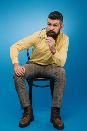 Photo for Handsome bearded man sitting on chair isolated on blue - Royalty Free Image