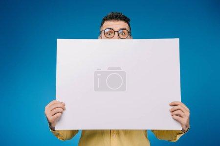 Photo pour Bel homme tenant une pancarte vierge isolée sur bleu - image libre de droit