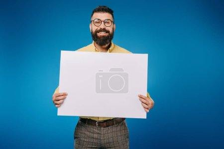 Photo for Cheerful man holding blank placard isolated on blue - Royalty Free Image