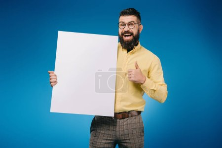 happy bearded man showing thumb up and holding empty board isolated on blue