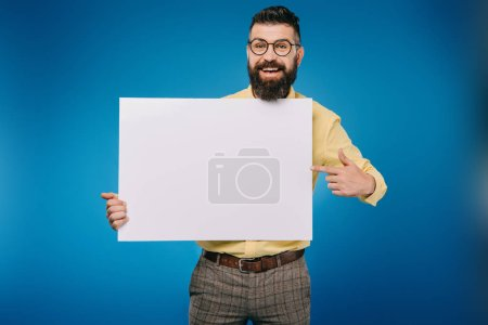 Photo for Cheerful bearded man pointing at empty board isolated on blue - Royalty Free Image