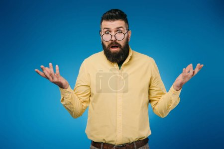 Photo for Bearded man in eyeglasses with shrug gesture isolated on blue - Royalty Free Image