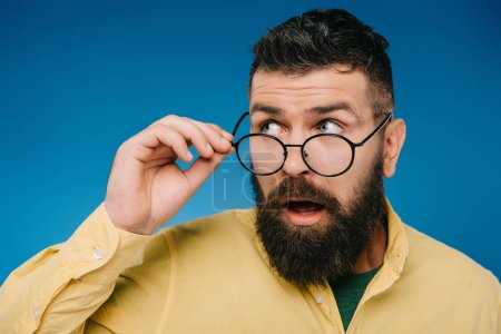 Photo for Surprised bearded man in eyeglasses isolated on blue - Royalty Free Image