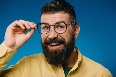 Photo for Smiling bearded man in eyeglasses isolated on blue - Royalty Free Image