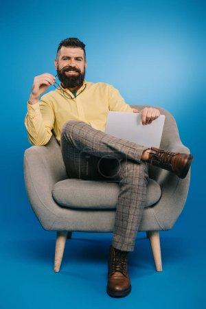 Foto de Guapo hombre de negocios sonriente sentado en sillón con portátil en azul - Imagen libre de derechos