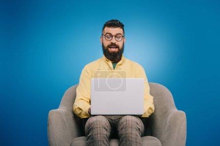 Photo pour Homme d'affaires excité à l'aide d'un ordinateur portable assis dans un fauteuil, isolé sur bleu - image libre de droit