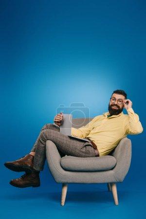 Lächelnder bärtiger Geschäftsmann im Sessel mit Laptop auf blauem Hintergrund