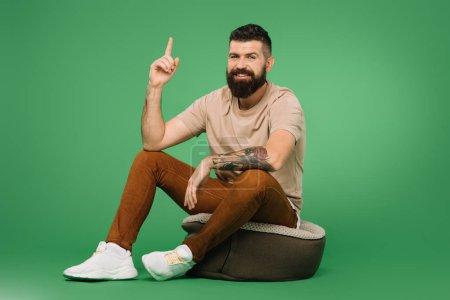 Photo pour Sourire bel homme barbu pointant vers le haut et assis sur le vert - image libre de droit