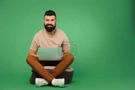 Photo for Bearded man using laptop isolated on green - Royalty Free Image