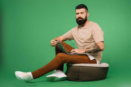 Photo pour Homme barbu confiant en utilisant ordinateur portable isolé sur vert - image libre de droit
