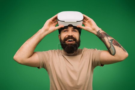 Photo pour Heureux homme barbu avec casque de réalité virtuelle isolé sur vert - image libre de droit