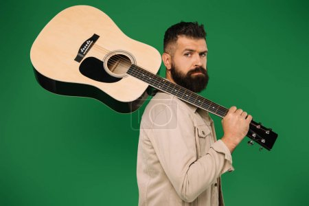 Photo for Bearded male guitarist holding acoustic guitar, isolated on green - Royalty Free Image
