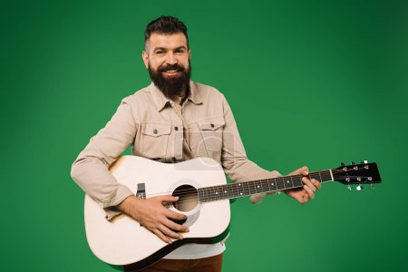 Photo for Cheerful handsome man playing on acoustic guitar, isolated on green - Royalty Free Image